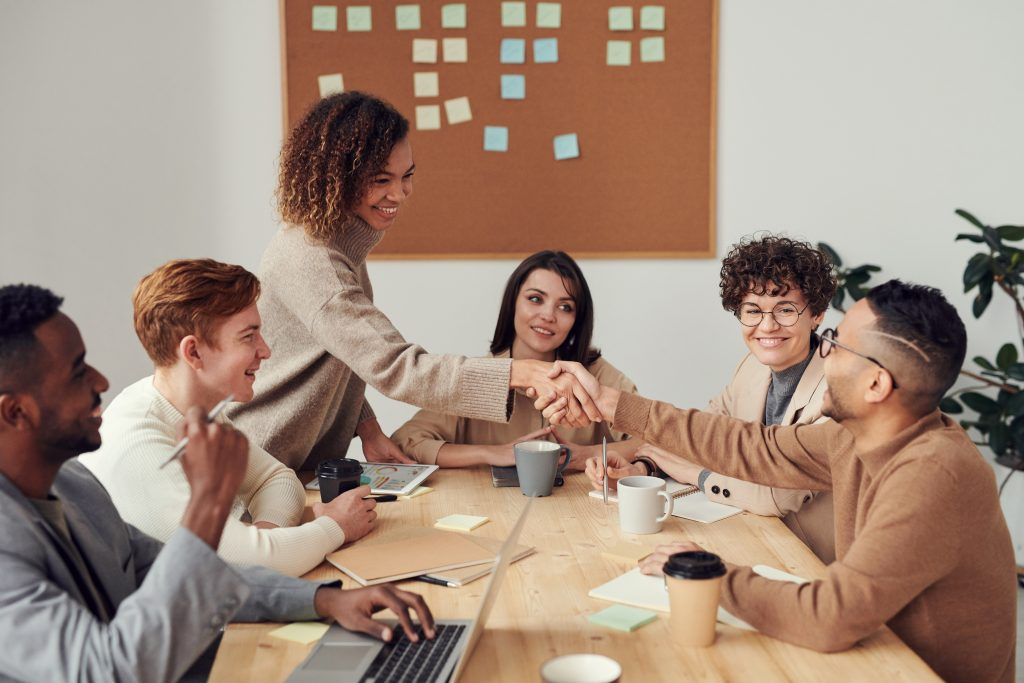 a group in a meeting chat, shake hands and smile with each other