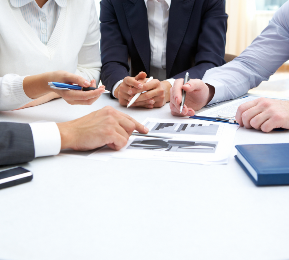 4 people gather around a table discussing the paperwork in front of them. their faces are not in frame.