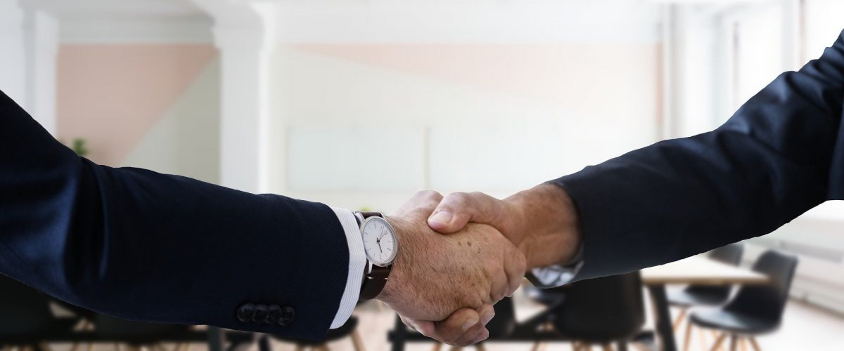 two men in suits engage in a handshake